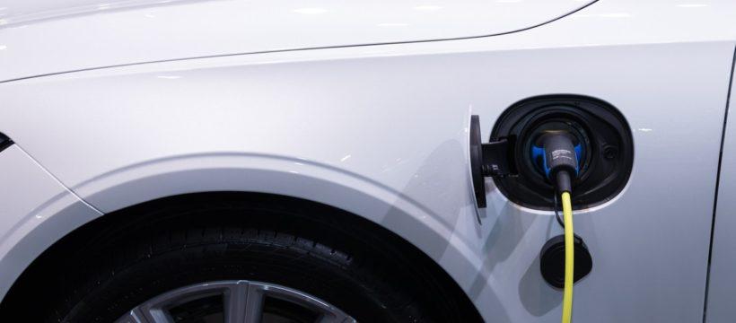 Hvid bil bliver opladet i garage i hjemmet