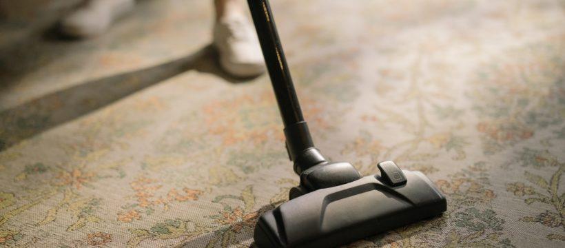 Person støvsuger i sit hjem på et gulvtæppe