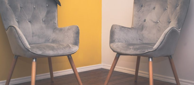 To stole står op ad en hvid og gul væg